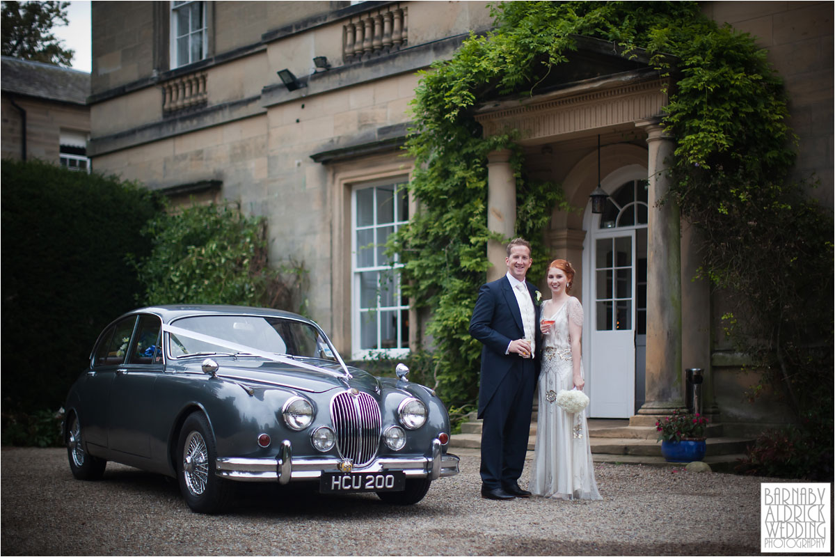 A wedding couple pose next to their vintage Jaguar outside Middleton Lodge in Yorkshire