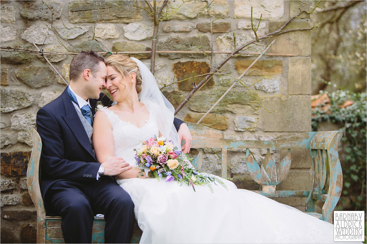 A Wedding photo of a couple kissing on a bench at The Pheasant Hotel in Harome near Helsmley in North Yorkshire