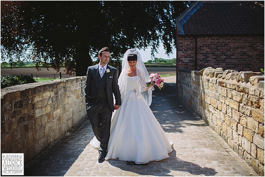 A wedding couple portrait walking around Priory Cottages wedding venue near Tadcaster and Wetherby in Yorkshire