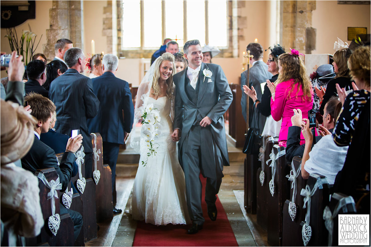 A wedding ceremony photograph walking down the aisle before heading to Priory Cottages near Tadcaster and Wetherby in Yorkshire