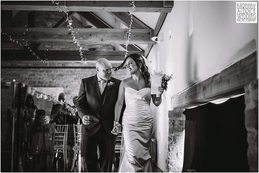 A wedding photograph of a couple walking down the aisle at Priory Cottages venue near Tadcaster and Wetherby in Yorkshire