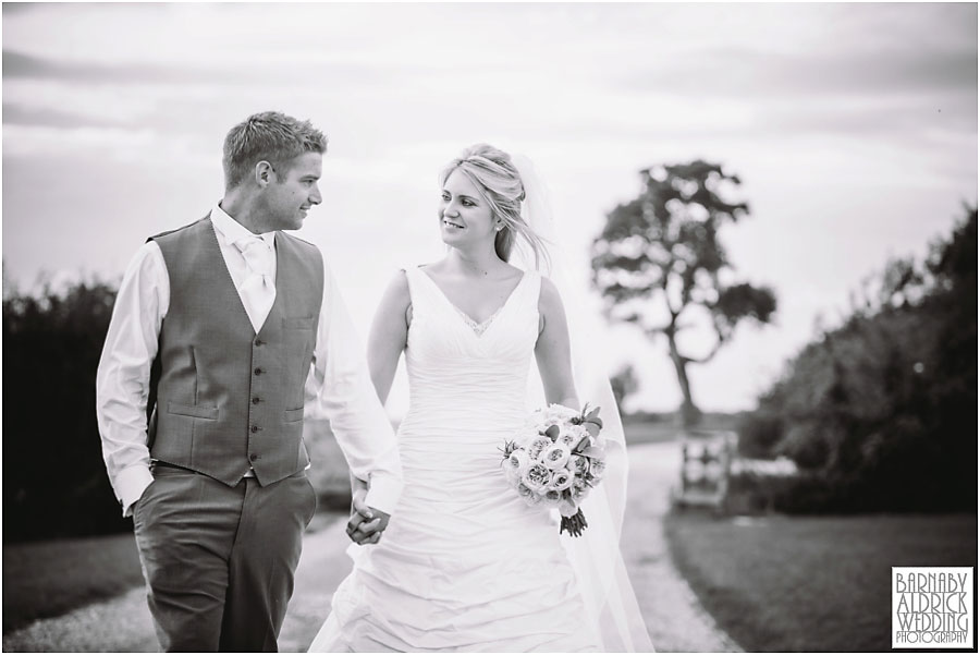 A wedding photograph of a couple walking together at Priory Cottages wedding venue near Tadcaster and Wetherby in Yorkshire
