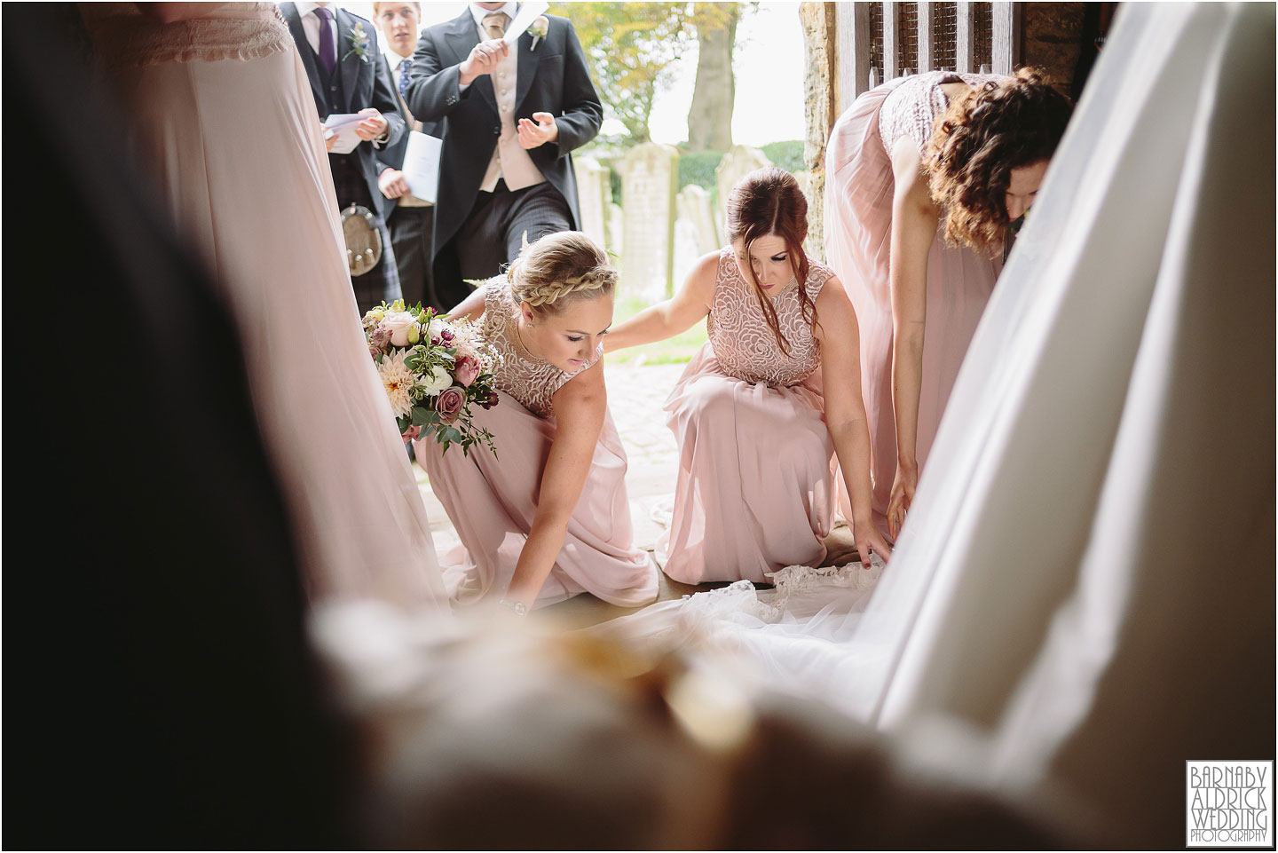 Bridesmaids adjusting the wedding dress