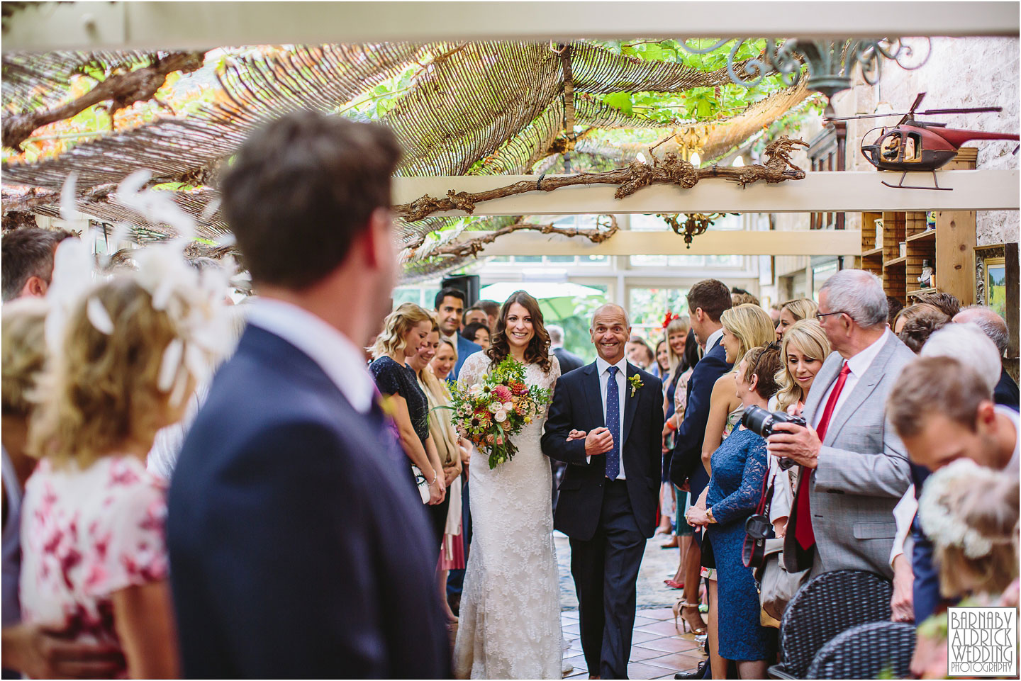 A bride walking down the aisle at her wedding ceremony at The Crab and Lobster in Yorkshire