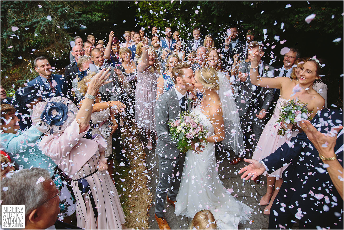 A Wedding photo of the confetti being thrown at St Helen's Church at Denton Hall in Yorkshire