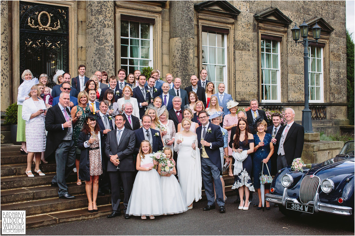 A Wedding group photograph of everyone on the stairs outside Denton Hall in Yorkshire