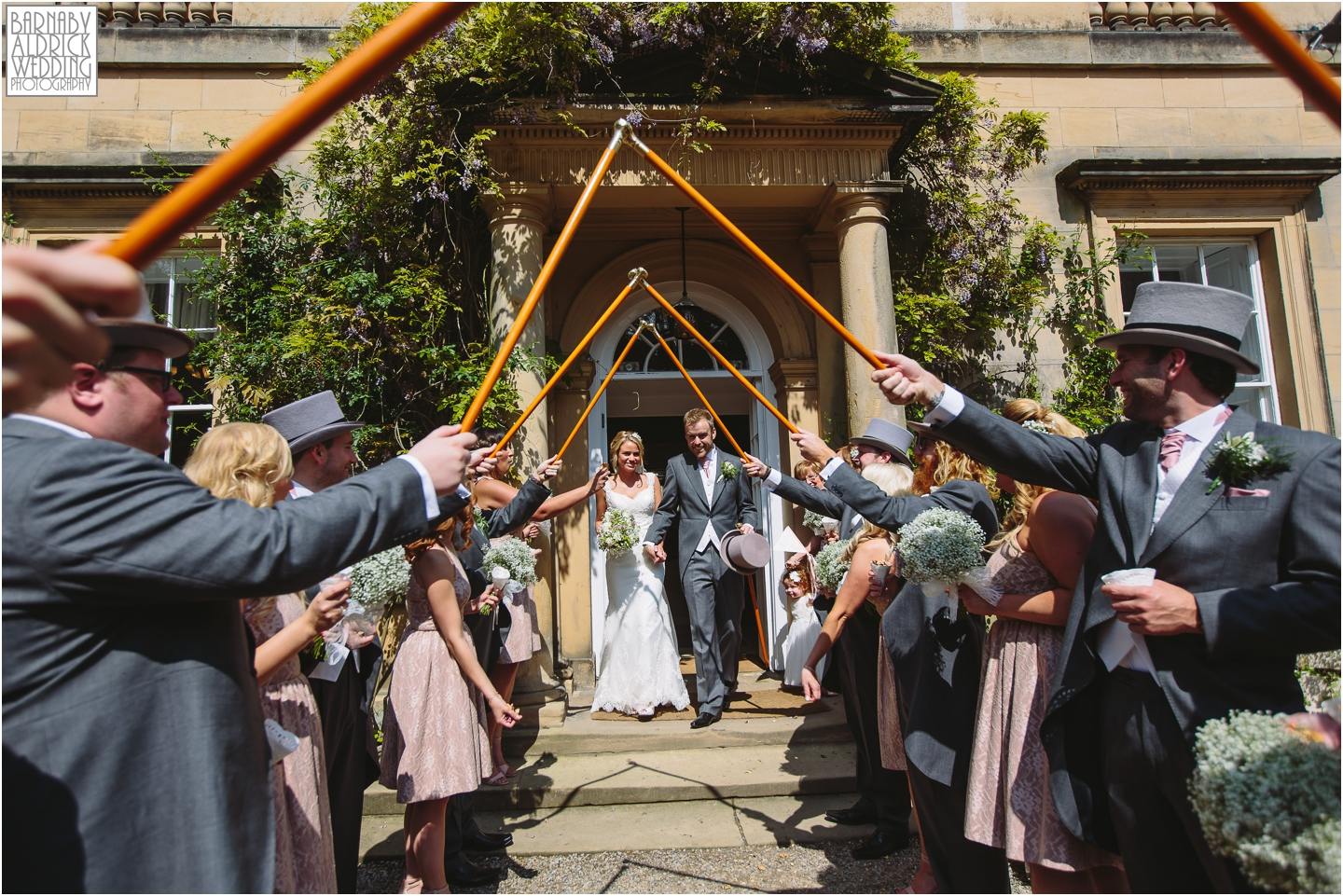 A walking stick guard of honour at a sunny wedding at Middleton Lodge
