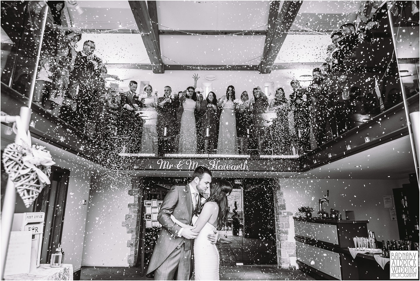 A black and white confetti shot of a couple kissing at Priory Cottages