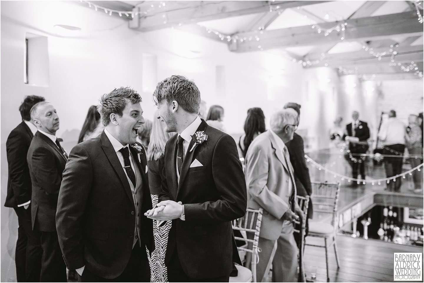 An excited groom turns to his best man to scream in glee at his wedding at Priory Cottages in Wetherby
