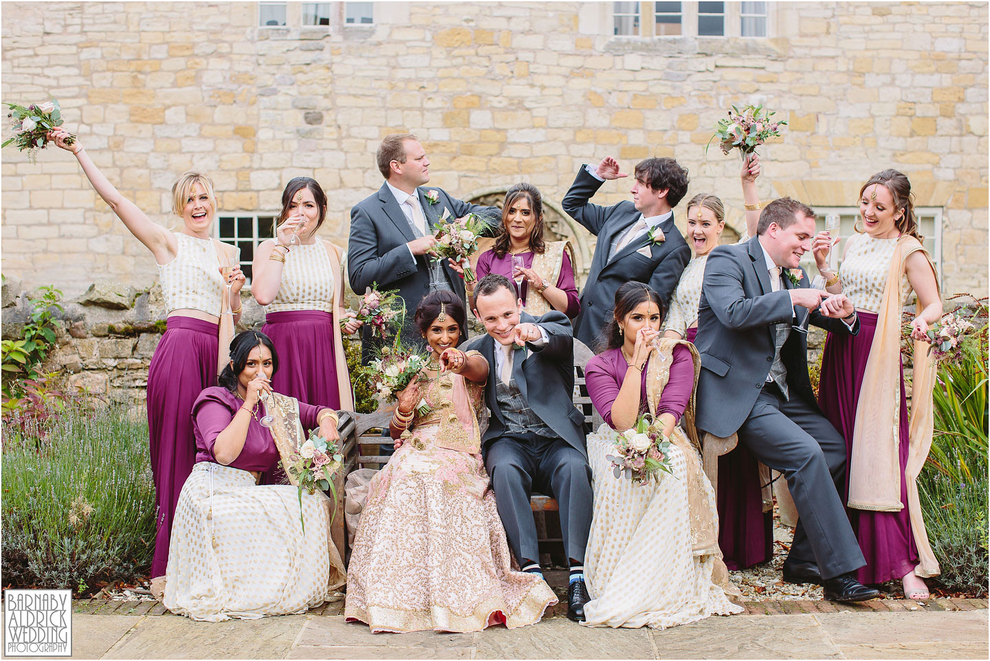 A funky groupshot at an indian wedding at Priory Cottages farm and barn in Yorkshire