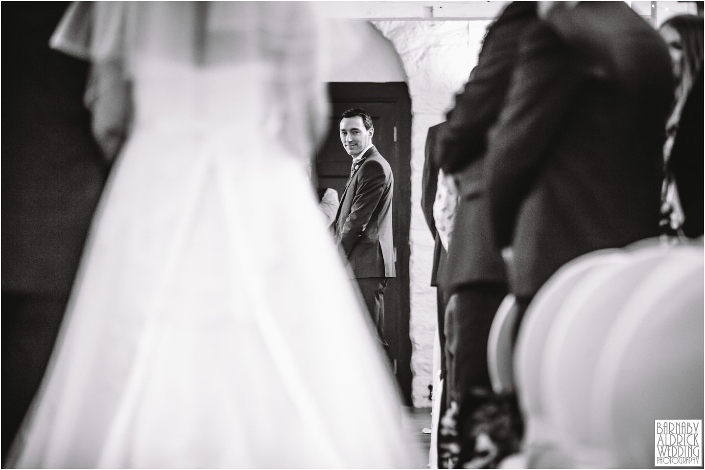 A groom watches the brides entrance at their wedding at Standedge Tunnel and Visitor Centre in Marsden
