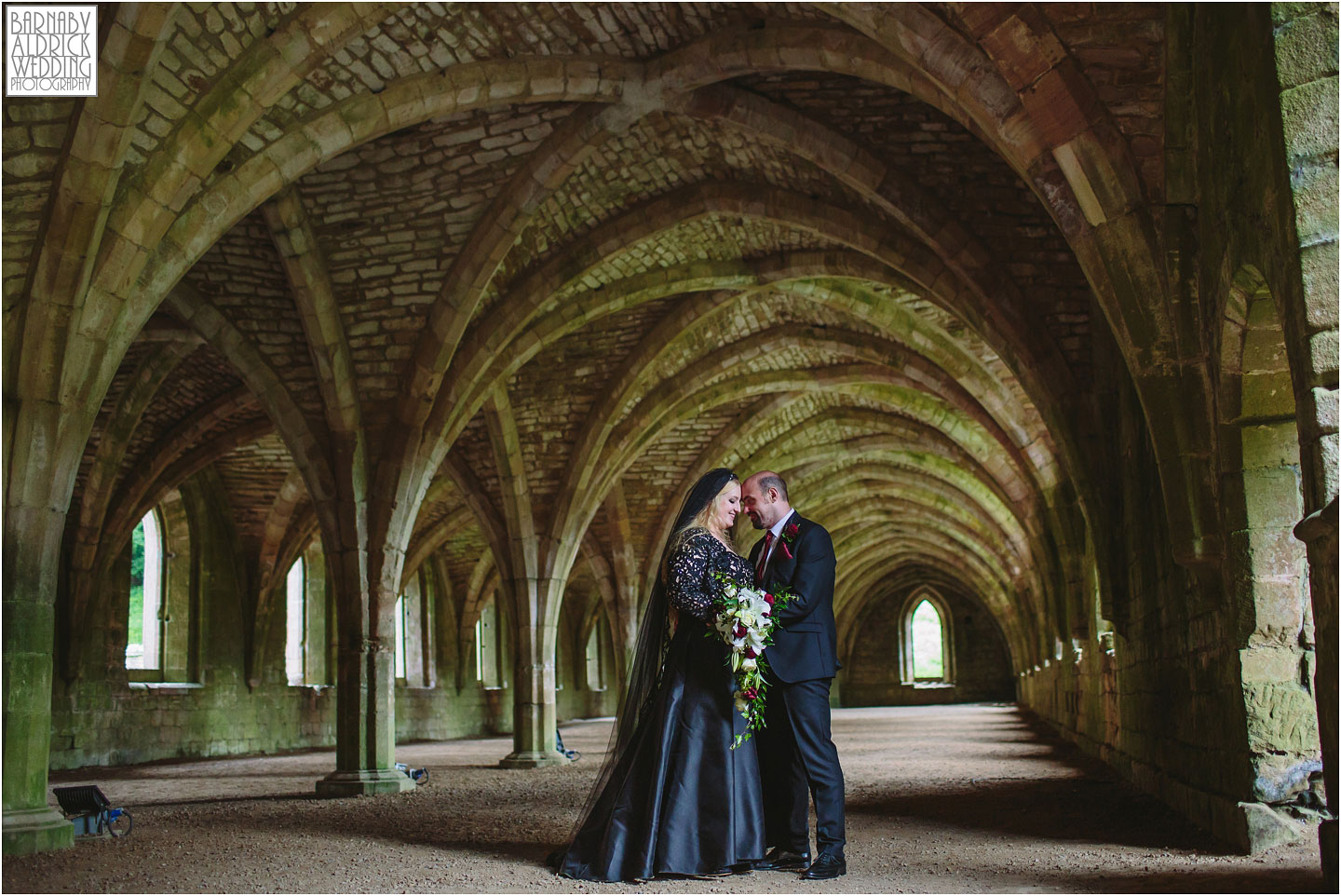 A wedding portrait photo in the cellarium of The National Trust's Fountains Abbey