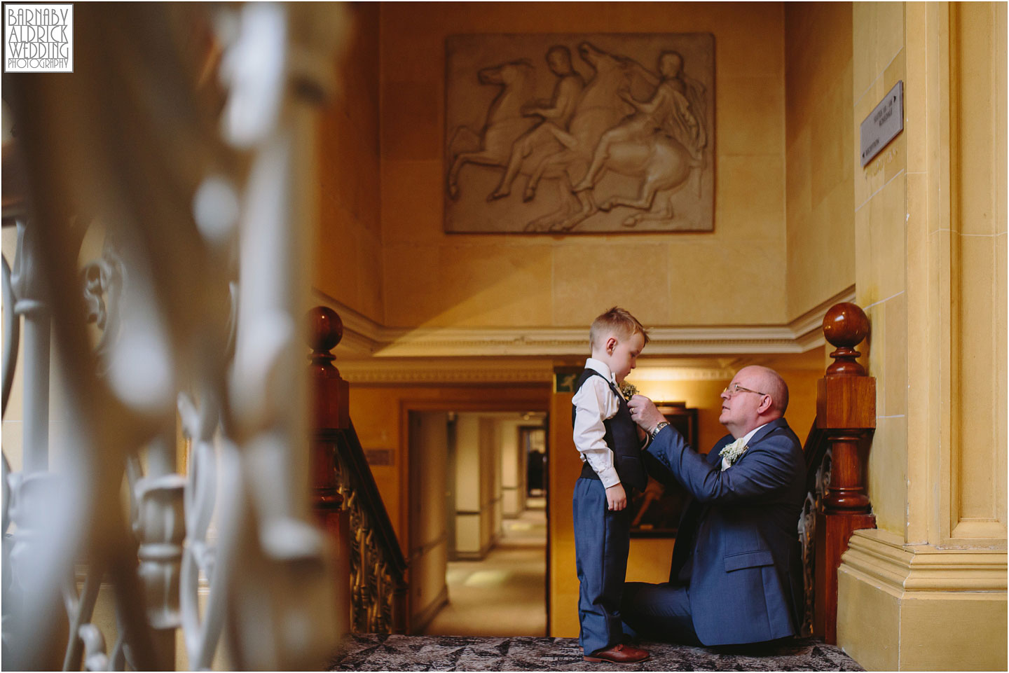 A wedding photo of a page boy having his button hole put on at Oulton Hall in Leeds
